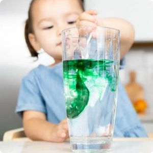 22-24 month old toddler stirring green food coloring into a water glass