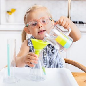 31-33 month old child pouring water from one container to another