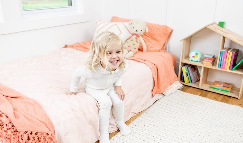 Young child sitting on their floor bed about to stand up.