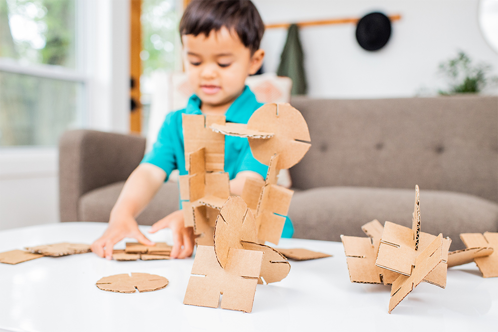 Young child putting together pieces of cardboard