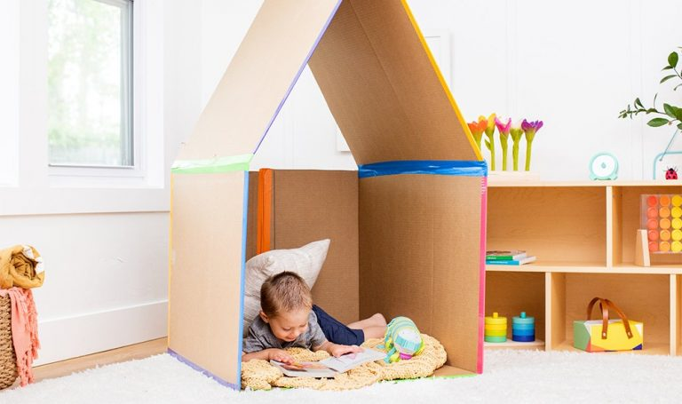 Toddler sitting in a cardboard box reading on a blanket