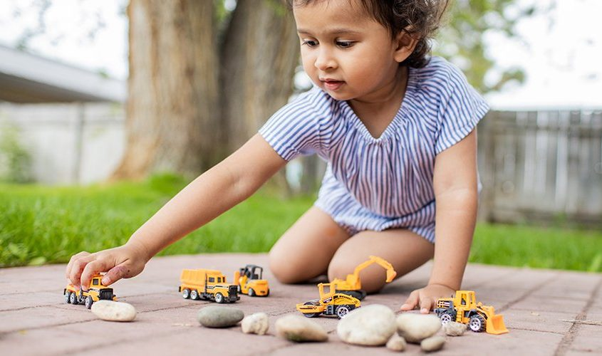 Toddler sitting outside playing with rocks and toy trucks