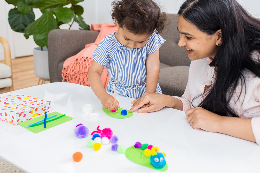 Toddler crafting with a woman at a table