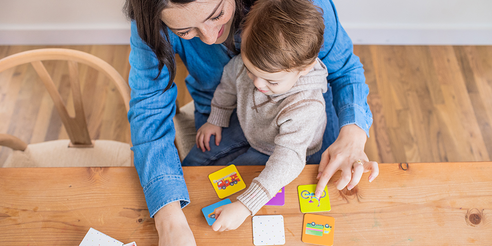 Toddler sitting on a woman's lap looking at the Memory Game cards by Lovevery