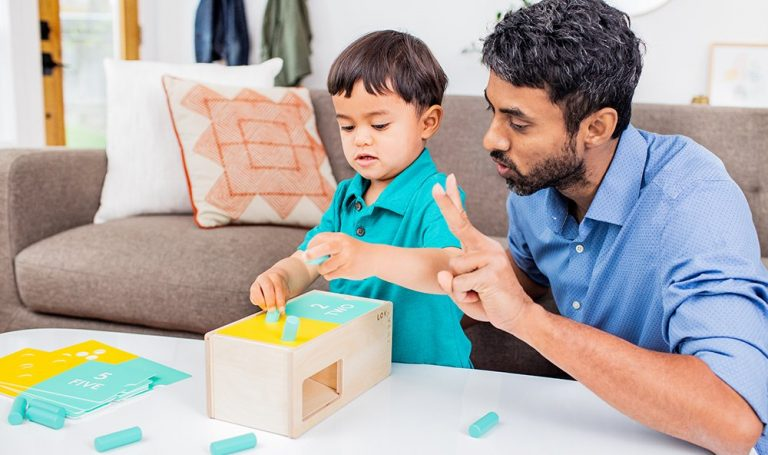 Toddler playing with the Wooden Counting Box by Lovevery