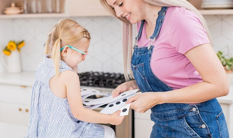 Young child and woman looking at cards with black dots on them