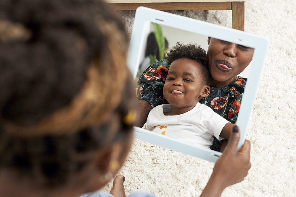 Young child sitting on a woman's lap while they look in a mirror sticking out their tongues