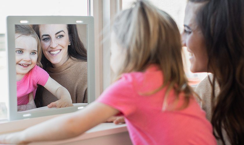 Toddler and woman looking at each other in a mirror