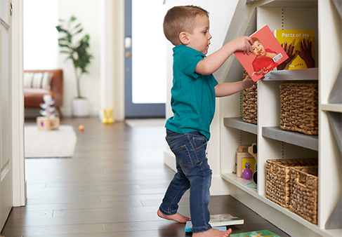 Young child putting a book by Lovevery away in a shelf