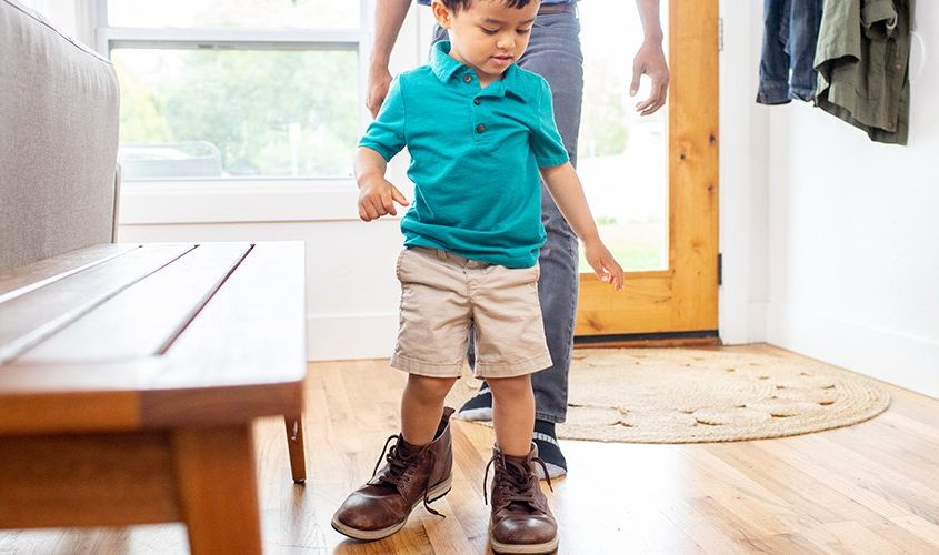 Young child wearing a men's shoes