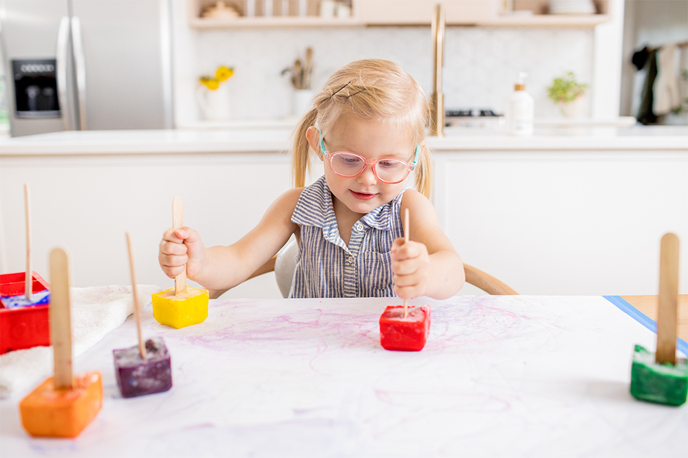 Toddler sitting at a table playing with colored ice on a piece of paper