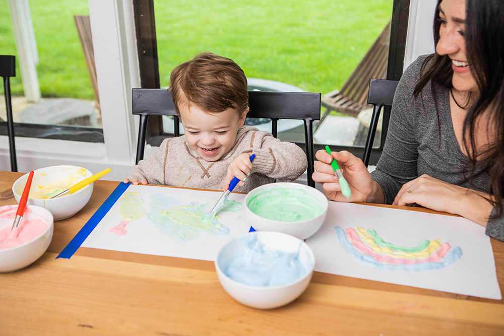 Woman and toddler playing with colored shaving cream on a piece of paper