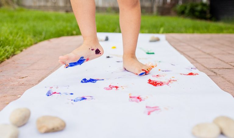 Young child with paint on their feet walking on paper