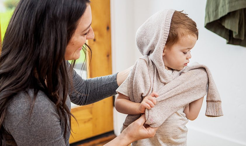 Young child putting on a sweater with help from a woman