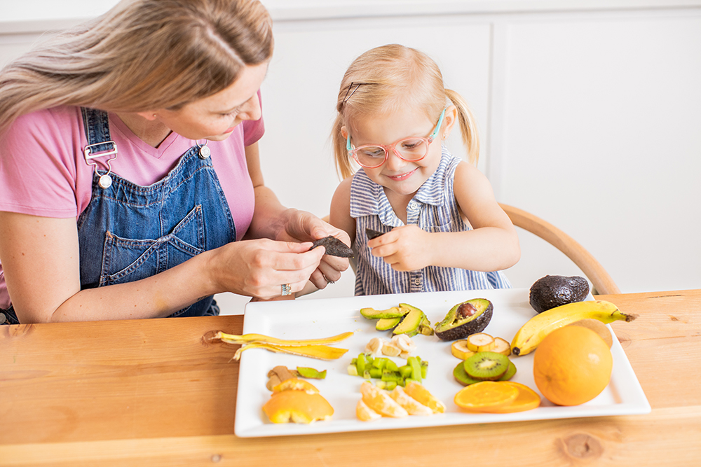 Woman and toddler looking at a tray filled with different fruits