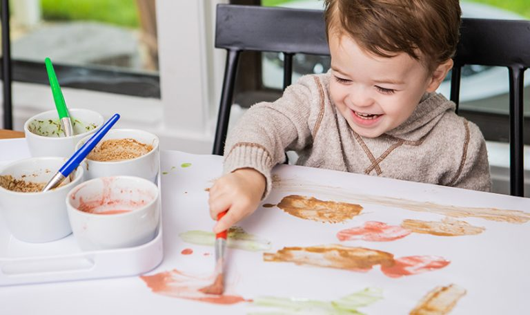 Toddler painting on a white piece of paper
