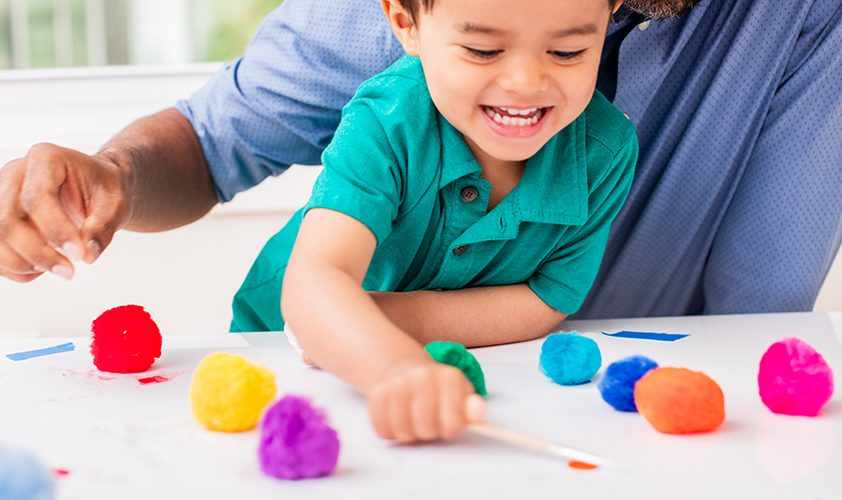 Toddler playing with pom poms and popsicle sticks on paper