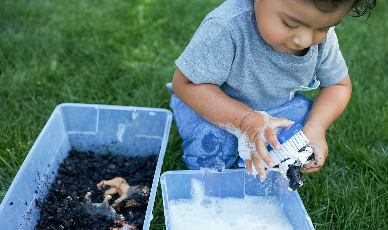 Toddler playing outside and washing an animal figurine that was in dirt