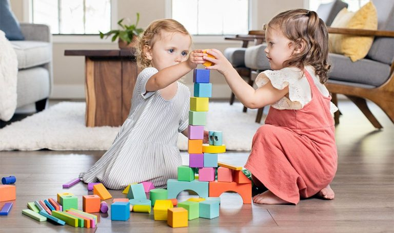 Two young children playing and stacking blocks from the Block Set by Lovevery