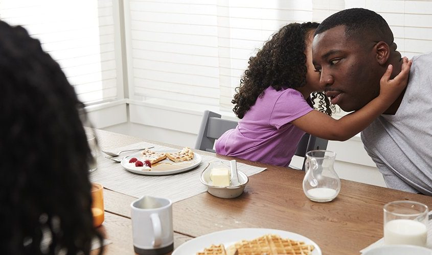 Family sitting at a table eating breakfast and the young child is telling a man a secret