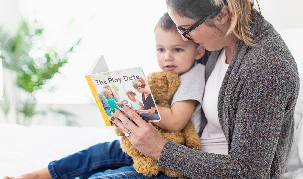 Woman holding toddler while looking at The Play Date book by Lovevery