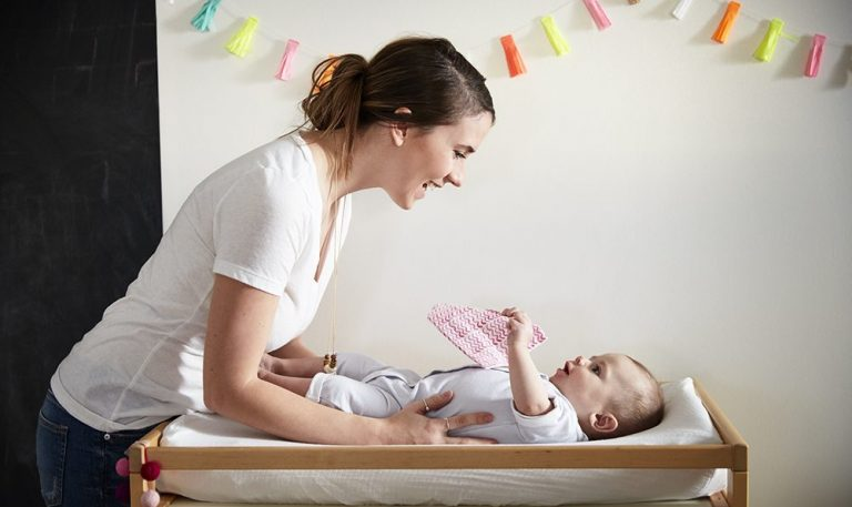 Woman looking down on a baby laying on a changing table