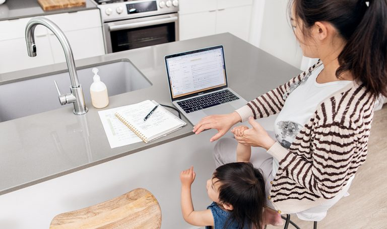 Woman on a laptop holding hands with a toddler