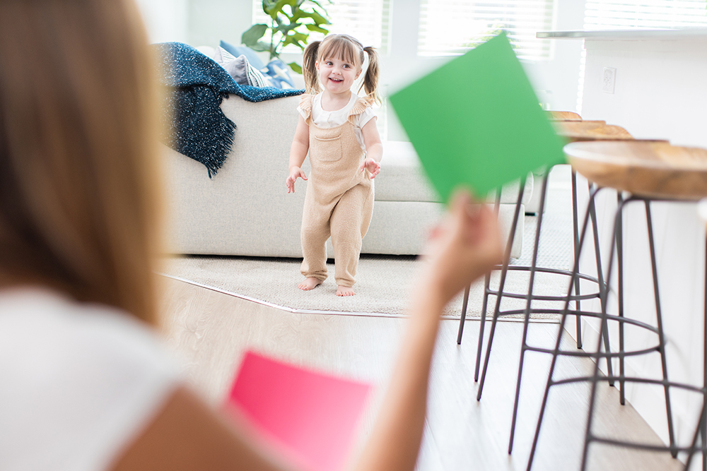 Toddler walking while a woman is holding up a green card