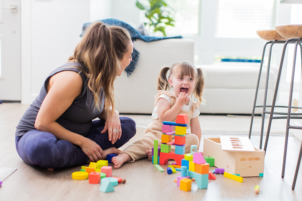 Young child and woman sitting on the floor playing with the Block Set by Lovevery