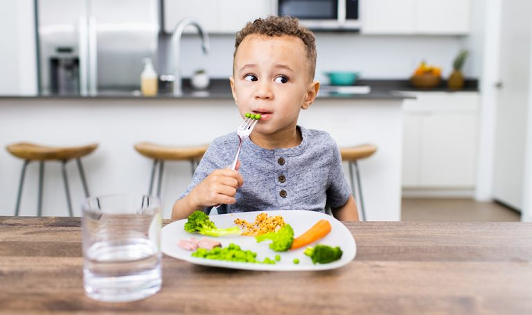 Young child eating vegetables while sitting at a table