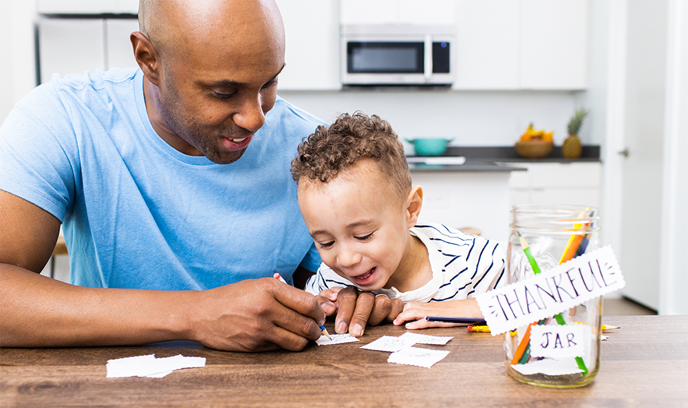 Young child sitting with a man writing things down on paper