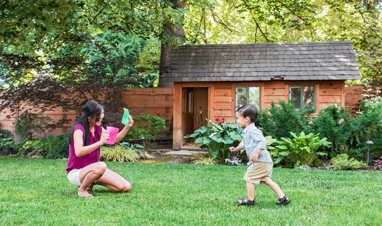 Toddler running to a woman outside while she holds a green card