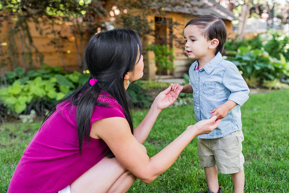 Woman holding hands with a toddler while standing outside in the grass