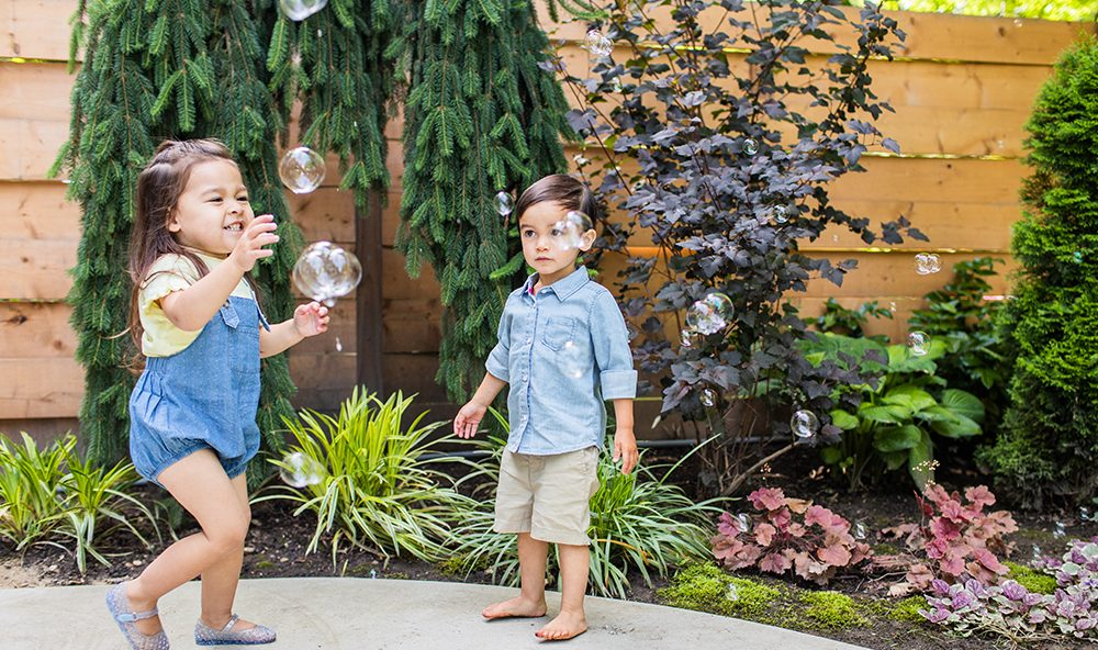 Two young children outside playing with bubbles
