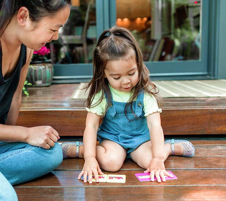 Toddler sitting on the ground outside playing with the Memory Game cards by Lovevery