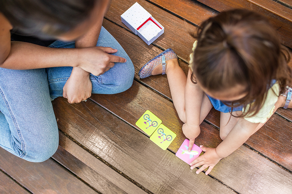 Toddler sitting on the ground outside playing the Memory Game and pointing to the air plane card
