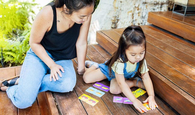 Toddler and woman sitting outside playing the matching game
