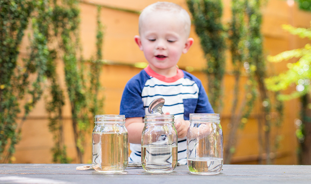 Toddler standing outside with three jars filled with water