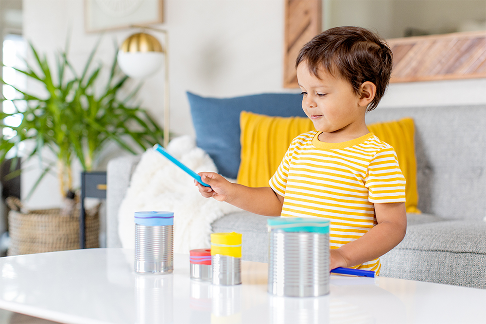 Toddler standing in front of a few canisters with a wooden stick