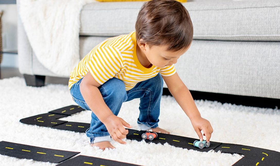Toddler pushing a toy car on a black road on carpet