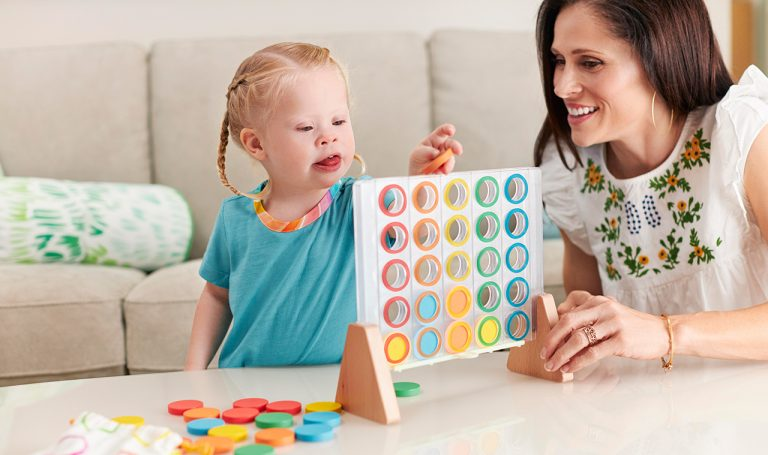 Young child playing with the Drop and Match Dot Catcher by Lovevery