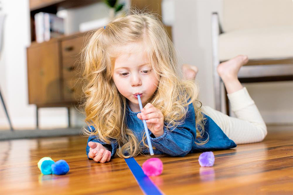 Young child blowing through a straw moving a pom pom