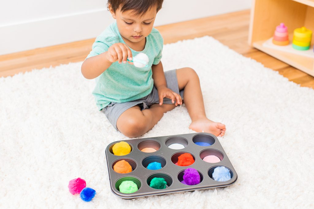 Young child picking up colorful pom poms from a muffin tin