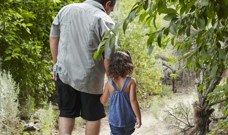 Young child and man holding hands while walking outside
