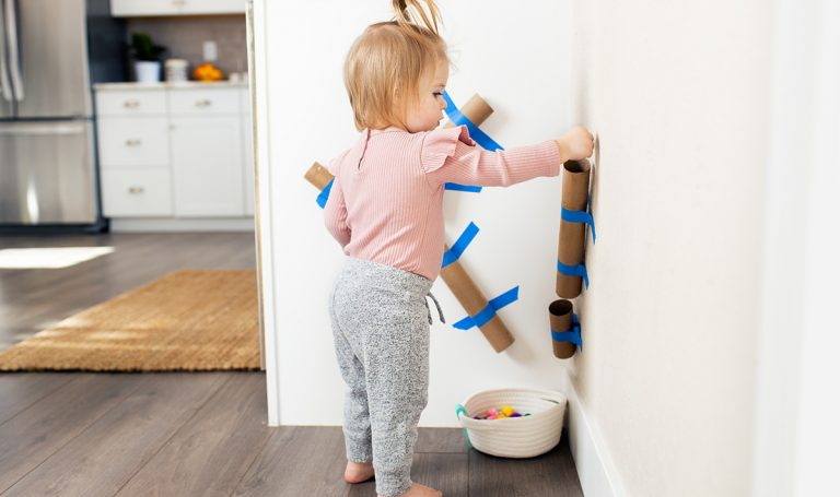 Toddler putting a ball through paper towel rolls that are taped to the wall