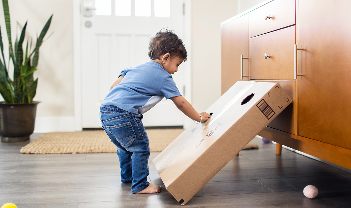 Toddler putting a ball in a cardboard box
