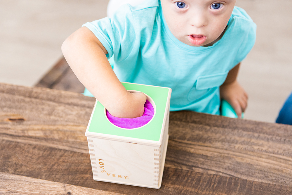Toddler putting their hand in the Magic Tissue Box by Lovevery