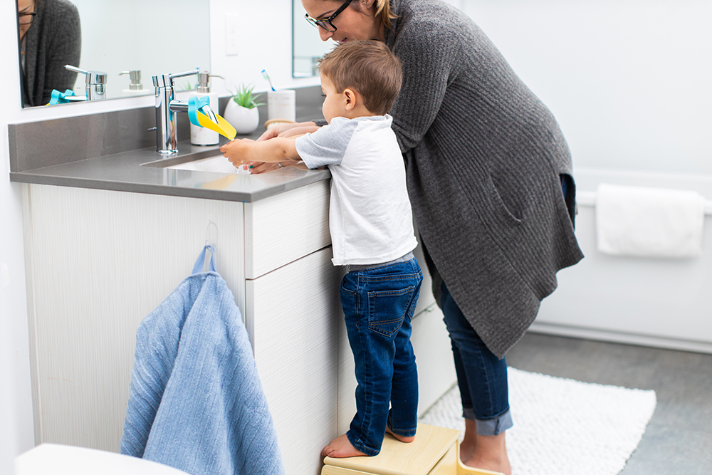Toddler standing on a stool washing his hands at the bathroom sink