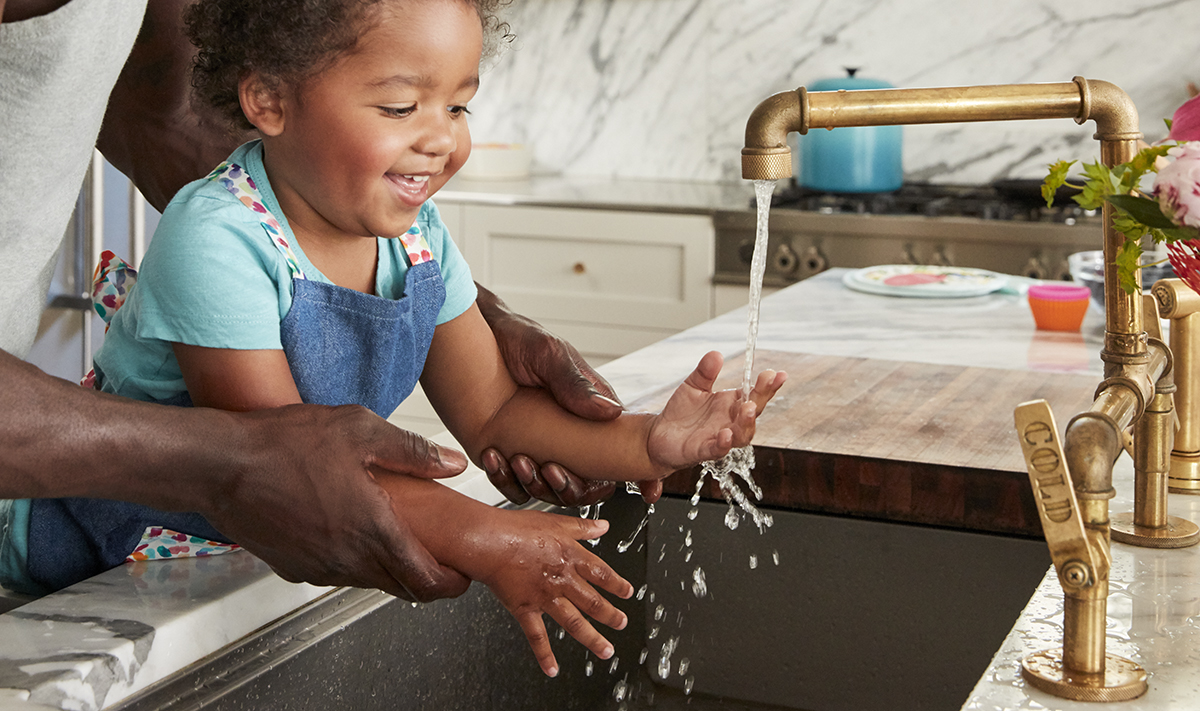 Toddler playing with water coming from the kitchen sink