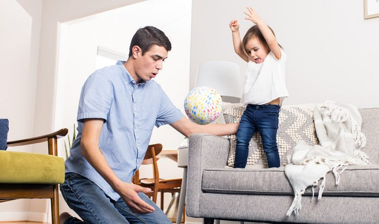 Young child throwing a ball off the couch while being supported by a man